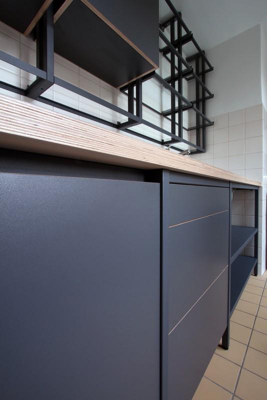 Op maat gemaakte stalen frame keuken met wandrek en open vakken. Het gepoederlakt staal is gecombineerd met multiplex dat tweezijdig is voorzien van HPL. Lades en keukenkasten zijn greeploos uitgevoerd.