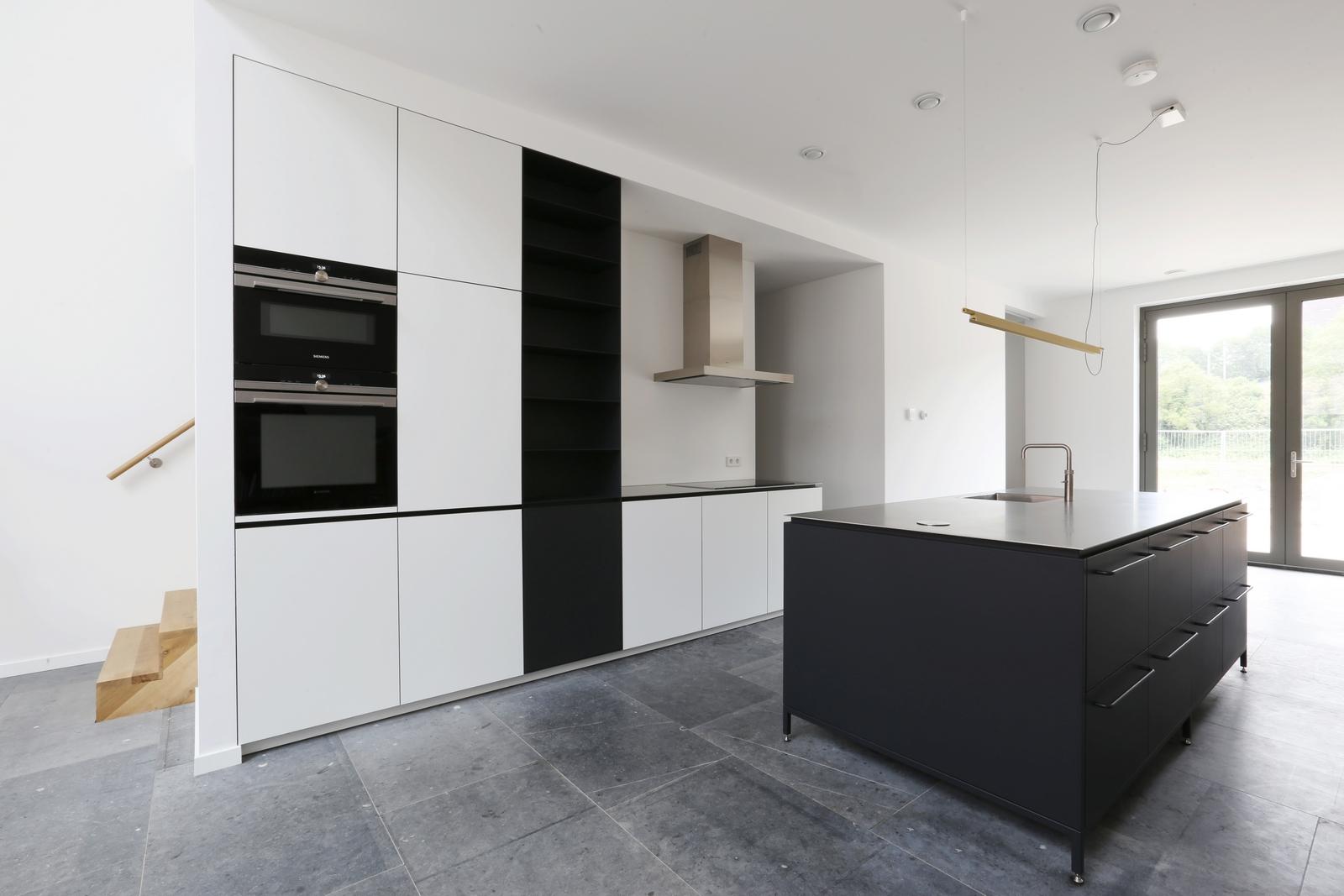 Keuken van staal en hout te Amsterdam. Met antraciet zwart gepoedercoat keukeneiland met RVS werkblad. Kastenwand van berken multiplex voorzien van HPL en stalen vakkenkast.