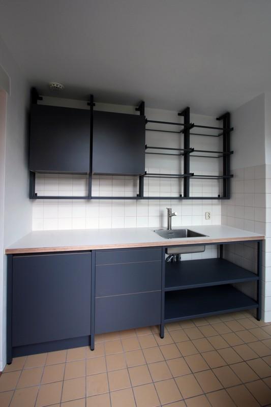 Op maat gemaakte stalen frame keuken met wandrek en open vakken. Het gepoederlakt staal is gecombineerd met multiplex dat tweezijdig is voorzien van HPL.