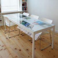 Stalen tafel op maat met glazen tafelblad en boekenvitrine afgewerkt met poedercoating/poederlak. Met onder het blad scharnierende kleppen voor het etaleren of bewaren van boeken.