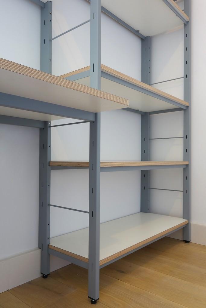 Op maat gemaakte stalen frame wandkast met bureau en ladeblok. Planken zijn van berkenmultiplex voorzien van HPL, het staal is gepoederlakt/gepoedercoat.