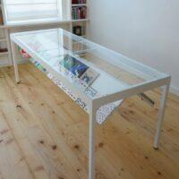 Stalen eet- en werktafel met boekenvitrine van gepoederlakt staal en extra helder gehard glas tafelblad